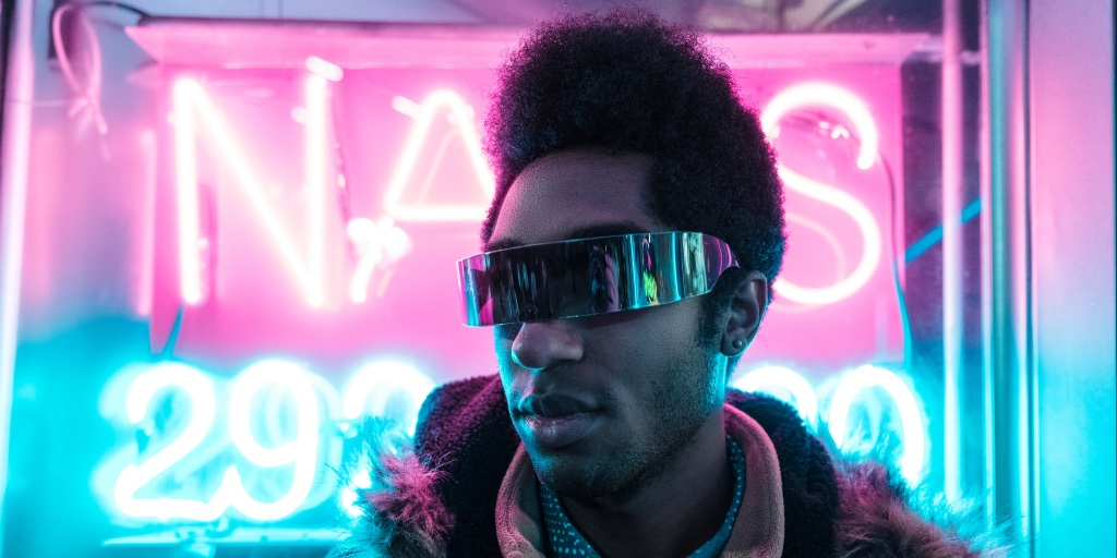 A portrait shot of a black man standing in front of two neon signs - one is hot pink, the other is blue. The dark-haired man is wearing futuristic sunglasses which appear to be a wrap-around strip of black metal.
