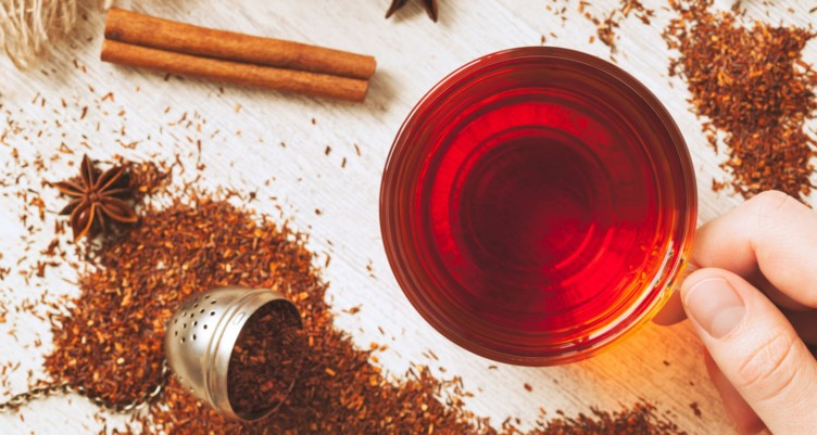 Aesthetic arrangement of cinnamon sticks, star anise, and rooibos tea powder, with a hand holding a cup of rooibos tea.