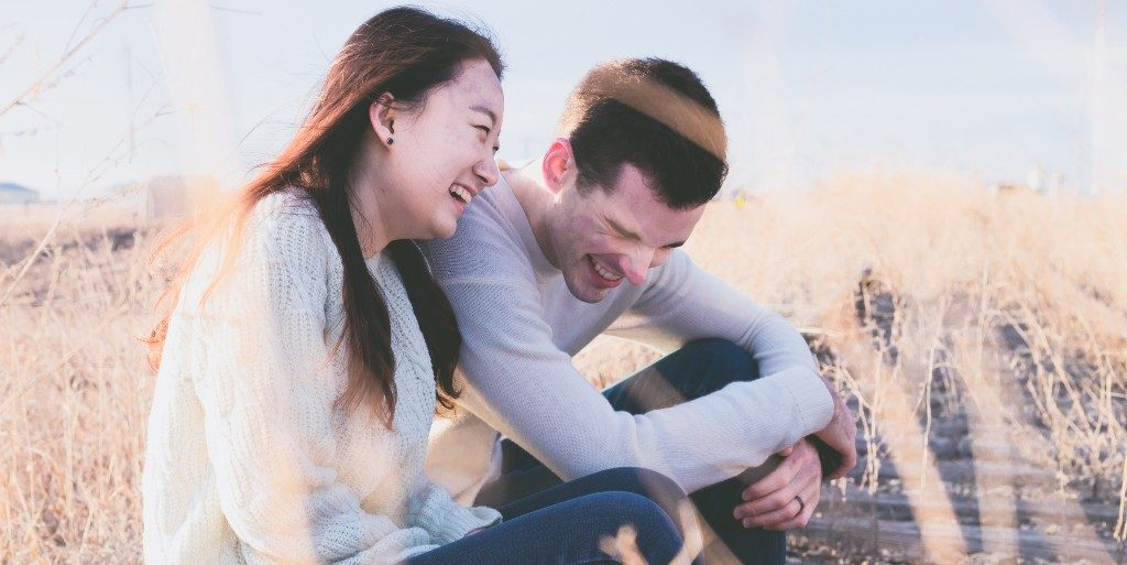 Asian woman in a white wool sweater and Caucasian man in a grey shirt laughing together in the fields.