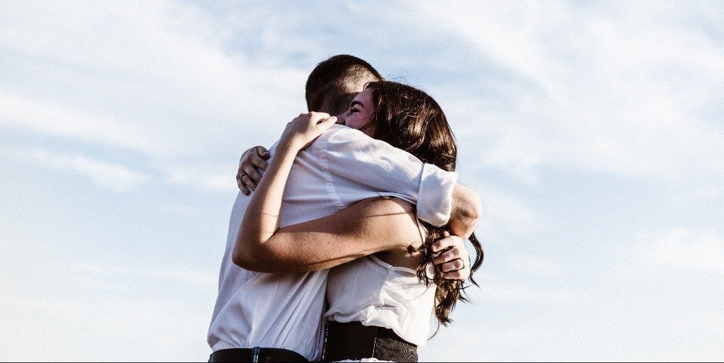 Man and woman both wearing white shirts hugging tightly.