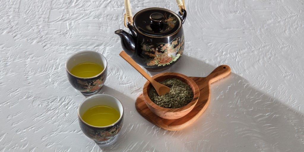 Two teacups filled with green tea, a black ceramic pot, and a wooden bowl filled with grounded tea leaves.