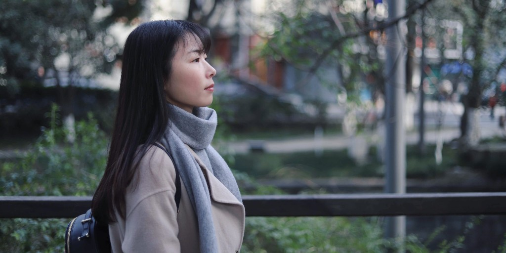 Asian girl wearing a beige wool coat and grey scarf standing sideways in front of trees.
