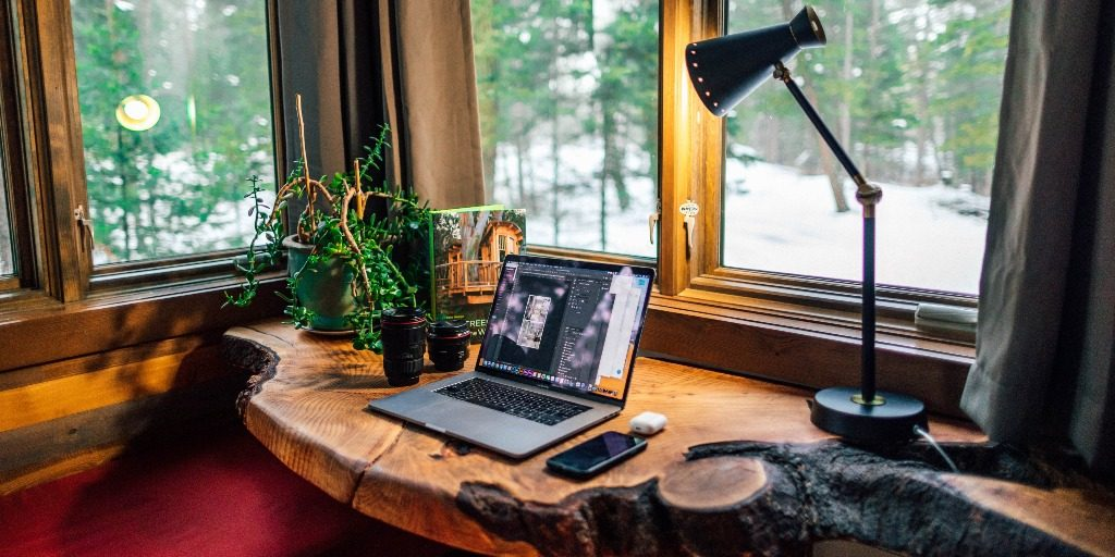 A rustic workplace facing a window with a laptop, plants, cellphone, and lamp on a desk.
