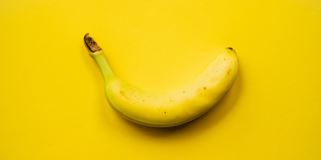 A yellow, unpeeled banana lies horizontally on a yellow surface.