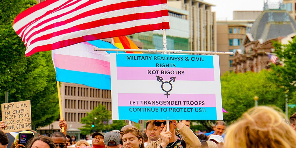 "[Image Description: person holds sign during march that reads ""Military readiness & civil rights, not bigotry. Let transgender troops continue to protect us.""] via Wikimedia Commons"