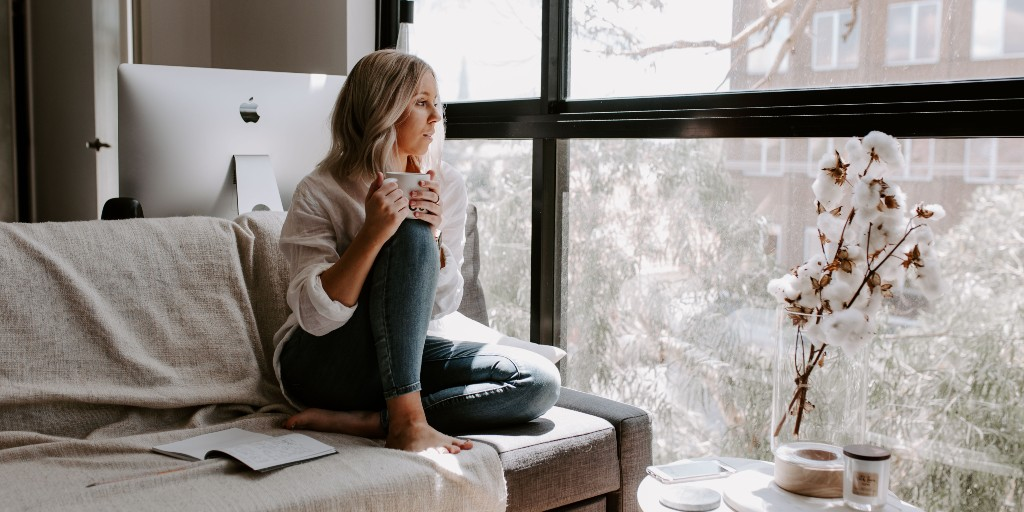 Woman sitting on a couch looking out the window holding a mug of tea. It's snowing outside.