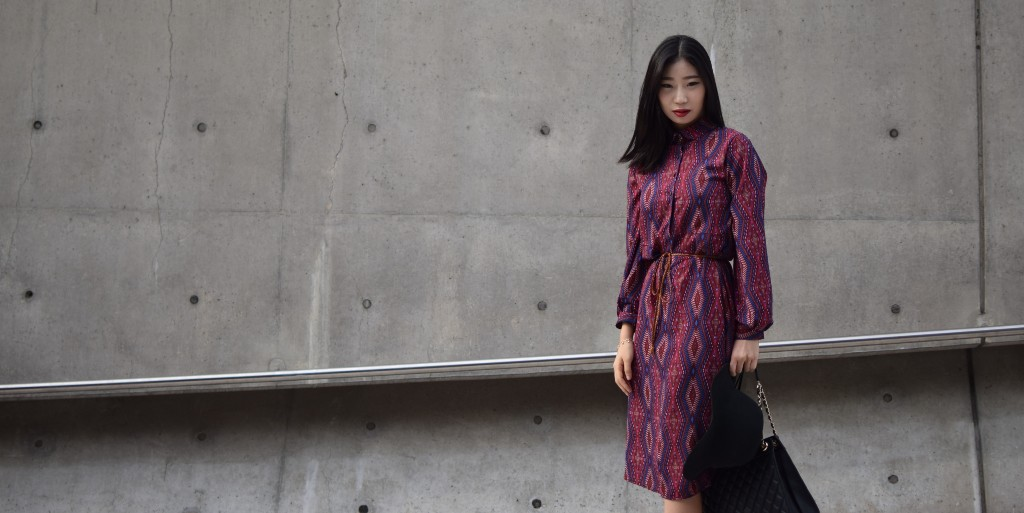 Asian girl wearing a red dress with purple and pink diamond patterns holding a black hat and handbag. She is standing behind a grey background and staring straight at the camera.