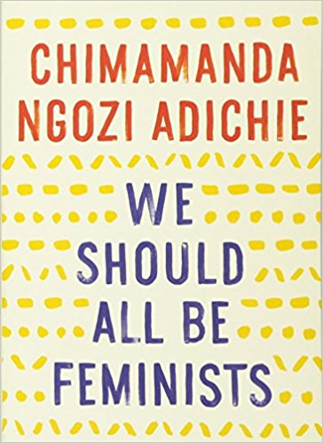 """[Image Description: Photo of the book cover of """"We Should All Be Feminists"""" by Chimamanda Ngozi Adichie. The book cover is beige with text in red and blue.] Photo via Amazon"""