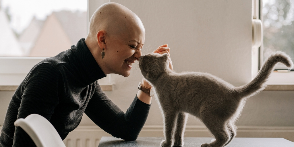 A woman with a shaved head, wearing a grey turtleneck, sits at a table playing with a cat who is standing on the table. They bump noses and the woman smiles