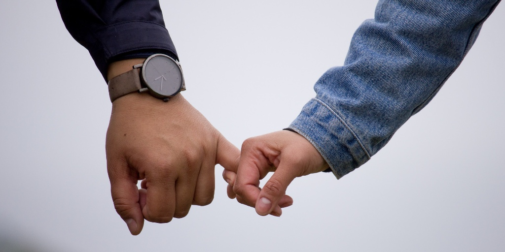 Two people are holding hands via their pinky fingers. One has a navy sleeve and leather watch, the other is sporting a denim sleeve.