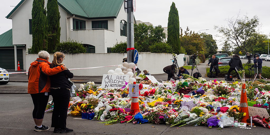 [Image Description: Women leaving flowers for mosque shooting victims.] Via Wikimedia Commons