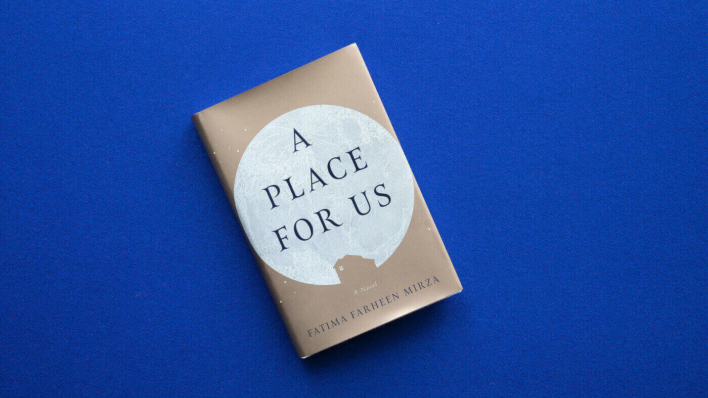 The novel 'A Place For Us' by Fatima Farheen Mirza lies against a bright blue background. The hardcopy cover is a dull gold colour, with a full moon in the centre of the book, and the small outline of a house in gold at the bottom of the moon.