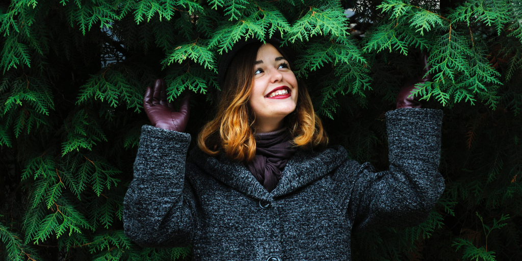 A brown haired woman is standing beside the tree and smiling. She is facing away from the camera