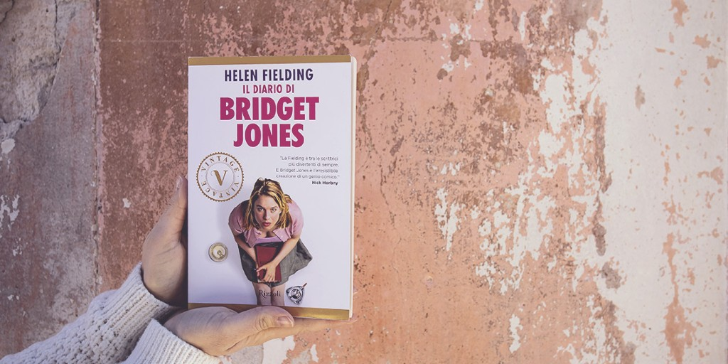 A person wearing a white sweater holds up the Italian copy of 'Bridget Jones's Diary' against a wall covered in different shades of dusky pink.