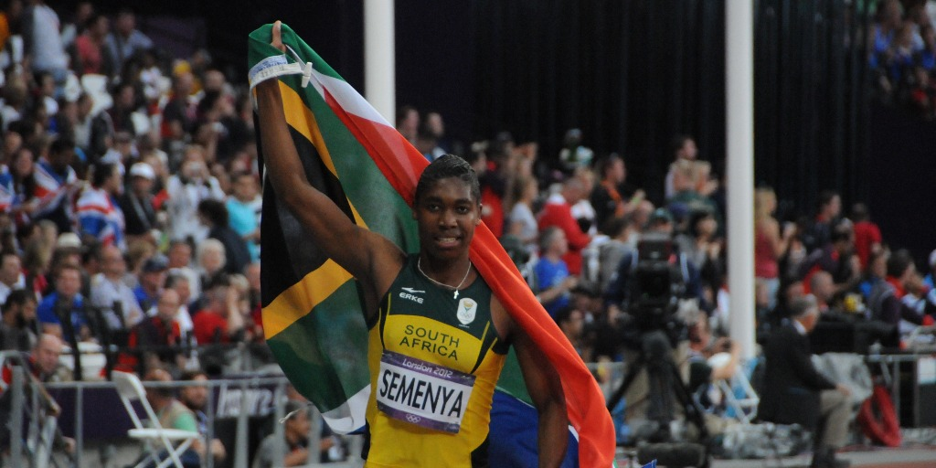 Caster Semenya holding up a South African flag around her after winning a race.