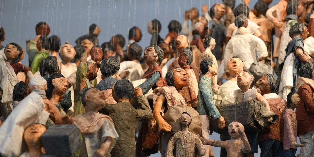 Paper figurines of refugees hung by thin threads suspend in air.