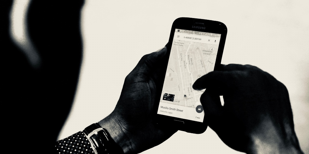 A black-and-white image shows a man using a navigational app on his smartphone.