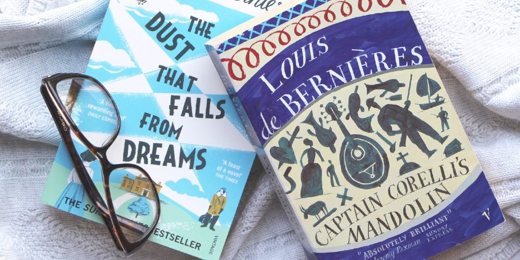 Louis de Bernières's novel 'Captain Corelli's Mandolin', featuring a blue cover with various symbols from the book on it, lies on a grey blanket alongside another one of the author's books and a pair of glasses.