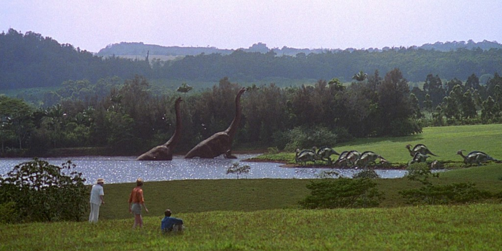 Three people in a grassy foreground are watching two long-neck dinosaurs walk out of a lake and another group of dinosaurs drinking water from the lake