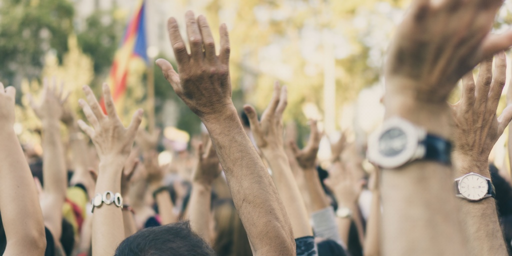 A large diverse group is gathered on the streets. The image shows a number of hands in the air.