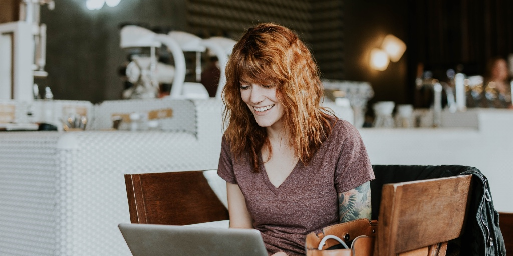 A red-headed woman sits in a coffee shop. She's using her laptop and smiling widely down at her screen as she types.