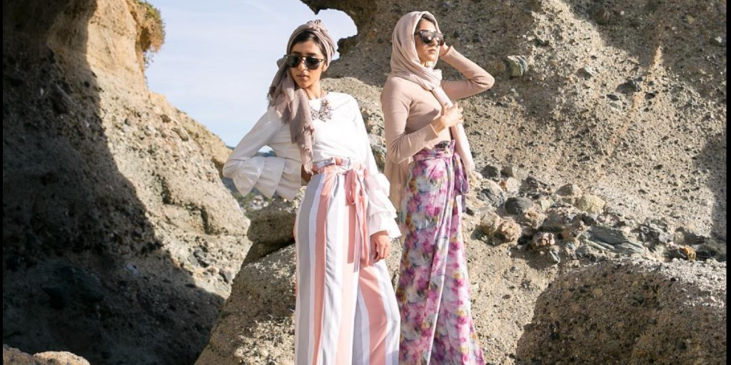 Two women, modeling Spring-themed modest clothing and headscarves are posing on a beach.