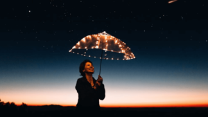A smiling woman holding up an umbrella with fairylights, underneath the nigh sky.