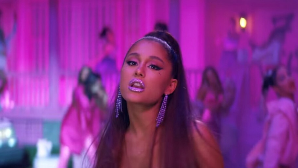 Ariana Grande, apparently a brown skinned woman, looking directly at the camera wearing purple lipstick, with a straight hair in a half up, half down do.