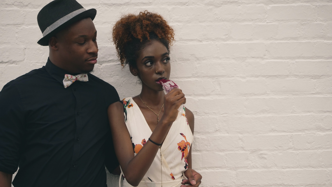 [Image description: Man holds woman around the waist while she eats a popsicle.] via Unsplash