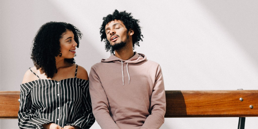 A couple is seated on a wooden bench against a white wall with the sun shining on them. The woman has shoulder-length curly hair and is wearing a black off-shoulder top. She is smiling and looking lovingly at the man, who is mid-speech, with his eyes closed and wearing a pink hoodie.