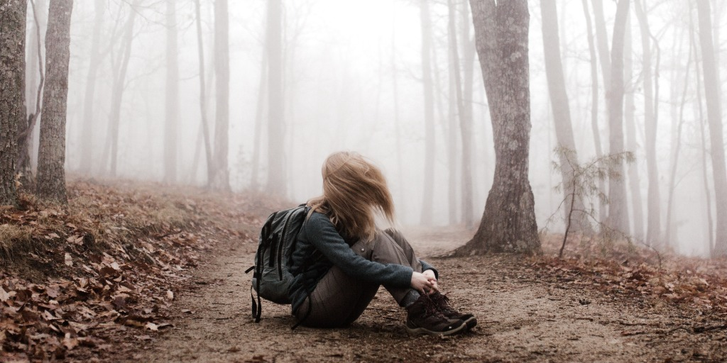 A woman with her hair flipped forward in a misty forest.