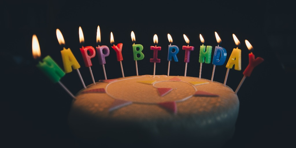 """A birthday cake with candles that read """"happy birthday""""."""