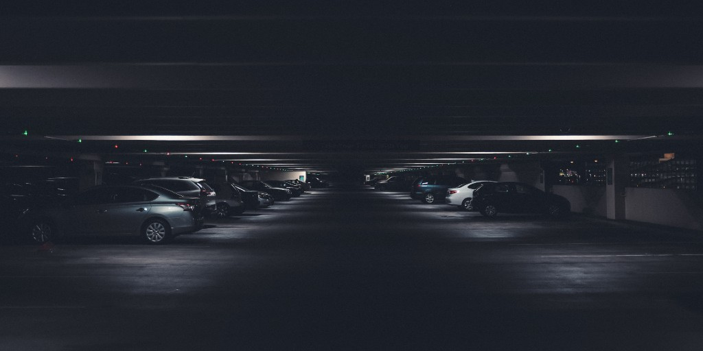A variety of cars parked in a dark garage with only small colored lights above each parking spot. The photo is very dark, taken in a setting of shadows.