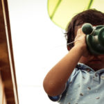 A young child looking through a microscope.