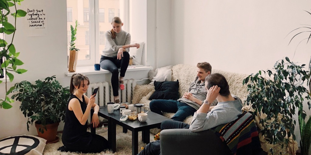 A group of people sitting in a living room talking to each other.