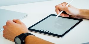 image description: a tablet is resting on a white table and a hand holding a smart pen is drawing on it