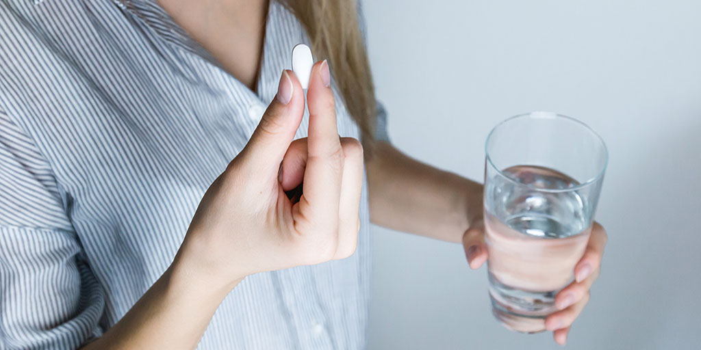 A woman holding a glass of water and medication