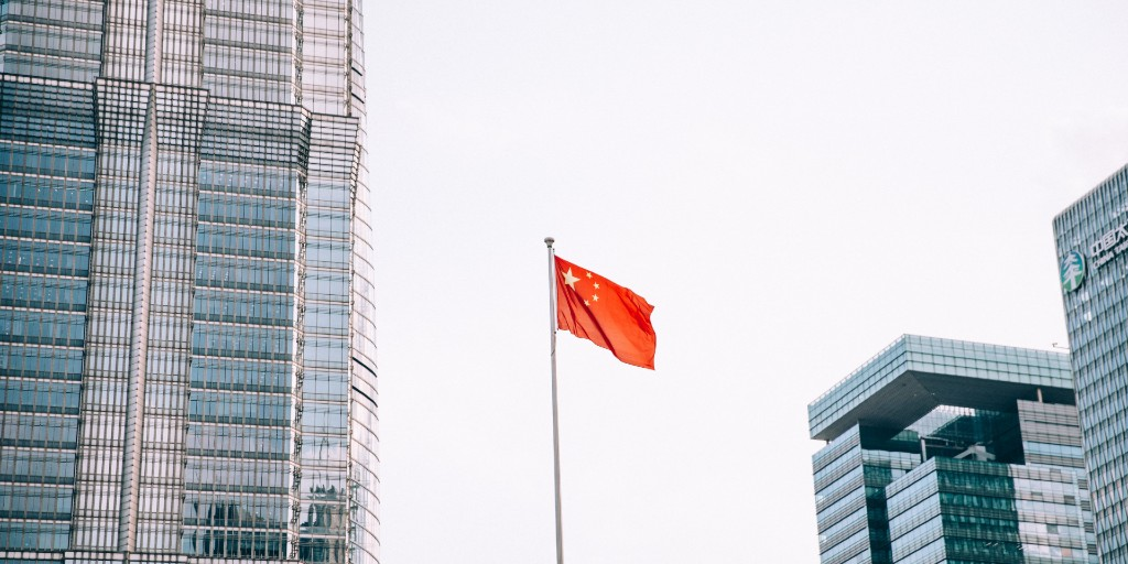 The Chinese flag hoisted up in the sky with buildings surrounding it
