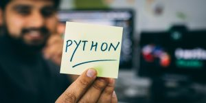 """image description: a man is holding a post it up to the camera with the words """"Python"""" written on it"""