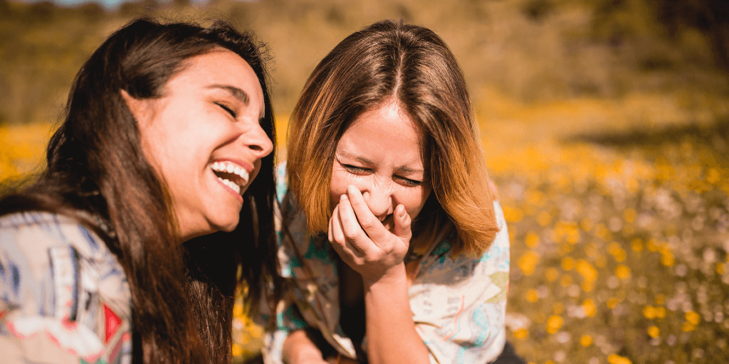 Two brown-haired woman sit outside in a field. They're both leaning into each other as they laugh.