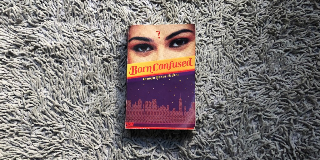 A copy of 'Born Confused' lies on a purple rug. The cover features a woman's eyes with a question mark at the centre of her forehead.