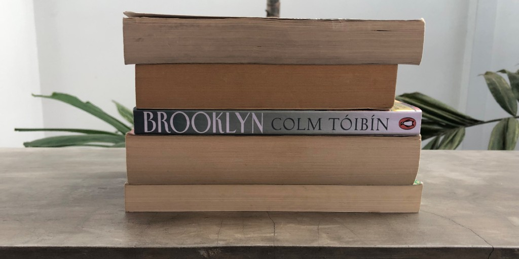 The spine of the novel 'Brooklyn' stands out among a pile of books, the rest of which are piled with their spines facing the opposite direction.