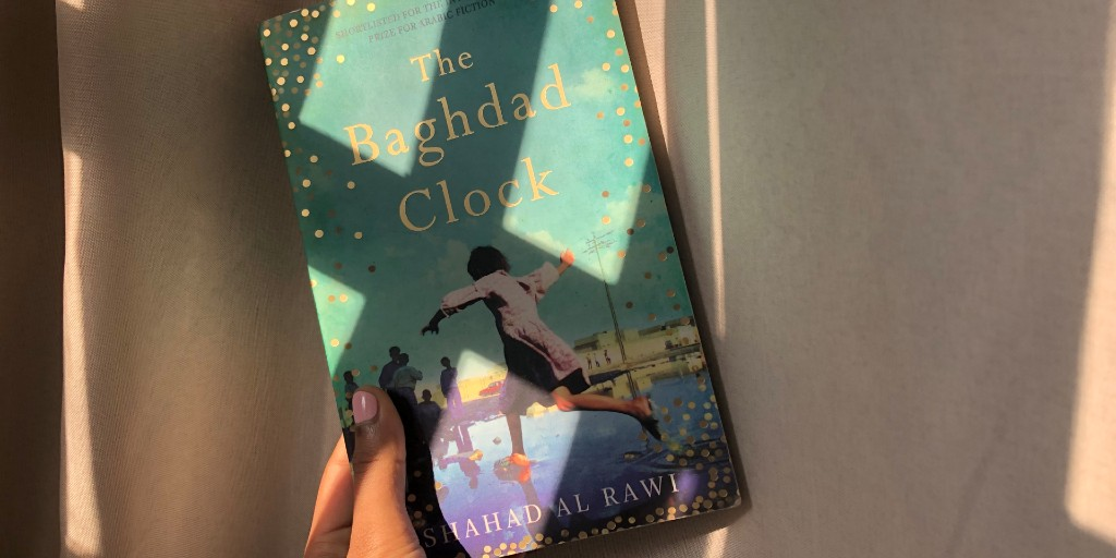 A hand holds up a copy of 'The Baghdad Clock' against a white curtain as patches of sunlight hit the book. The cover is shades of blue and features a young girl leaping over a puddle.