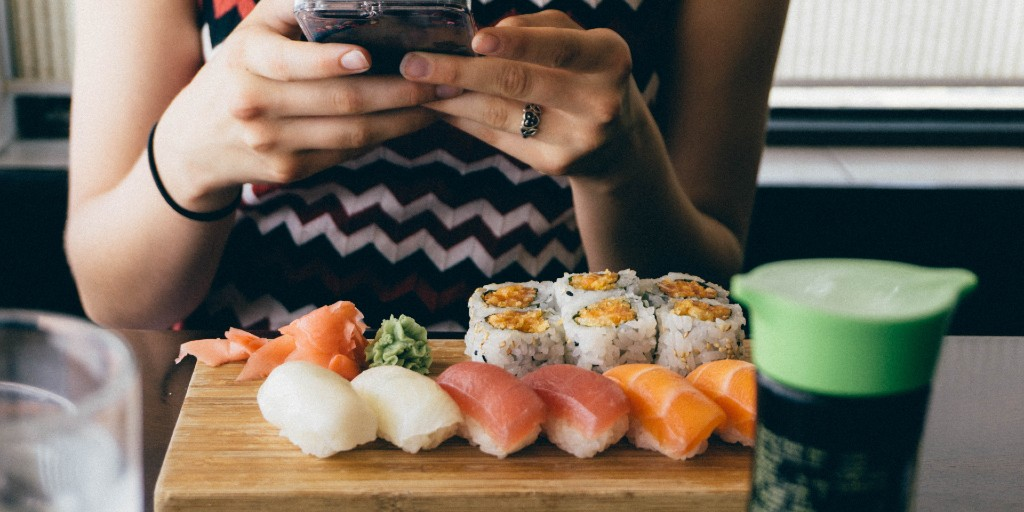 Girl taking a photo of a plate of sushi in front of her.