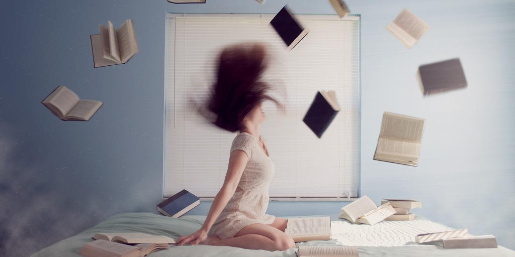 A woman flipping her hair back in bed with lots of books flying around her.