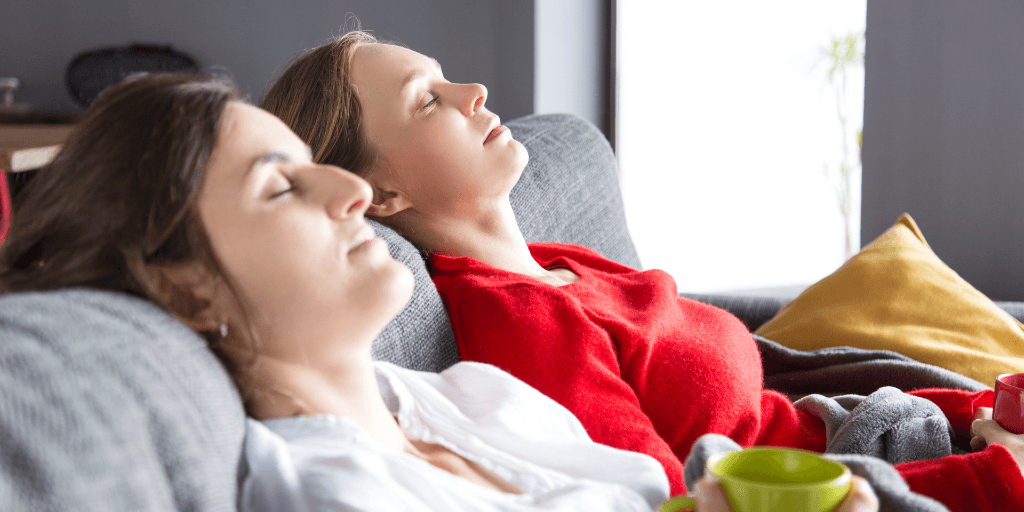 Two women are sitting side-by-side on a couch, reclined, in a sun-lit room. They both have their eyes closed.