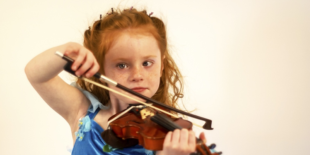 A young red-haired girl is playing the violin. She is in a blue dress.