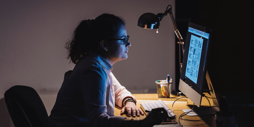 A dark-haired girl in a ponytail and glasses is sitting at her desk in the dark. She is working on her computer, late into the night.