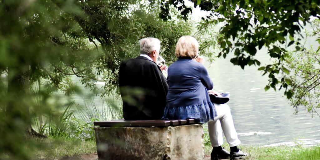 An old couple sitting on a bench surrounded by trees. Both persons hair is white and their backs are to the camera.