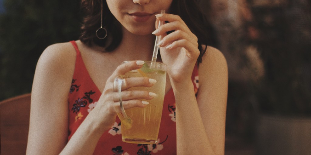 Girl holding an iced drink with a straw in her hands.